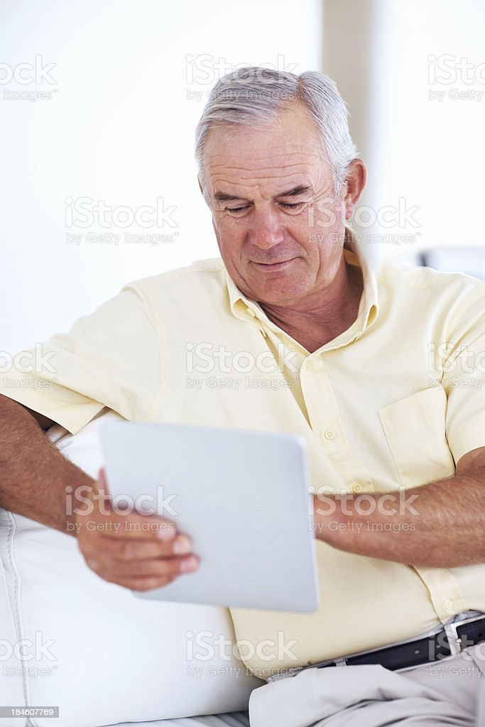 Senior man using tablet PC on couch royalty-free stock photo