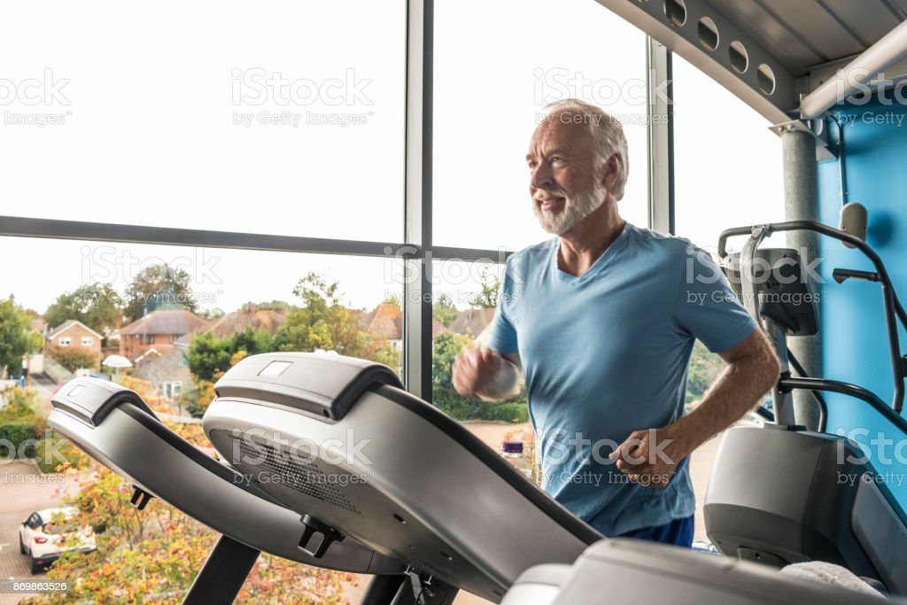 Senior man using treadmill in gym wearing blue t shirt stock photo