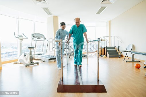 Man in his 70s in physiotherapy studio, woman watching and helping, man holding railings