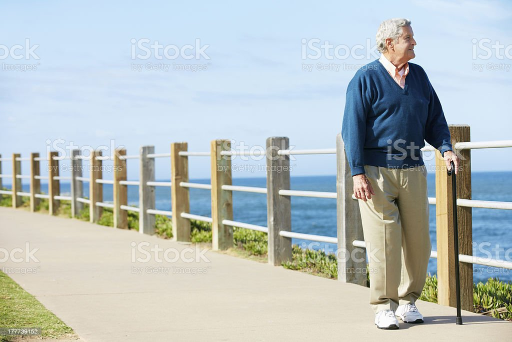 Senior Man Walking Along Path By The Sea stock photo