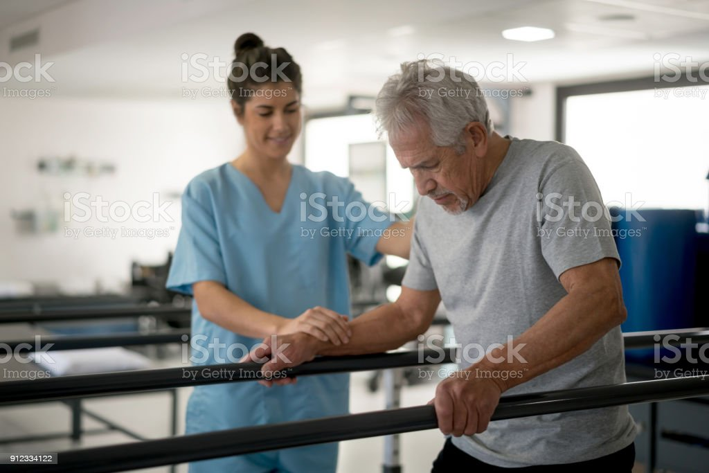 Senior man walking between parallel bars in physiotherapy and therapist next to him helping stock photo