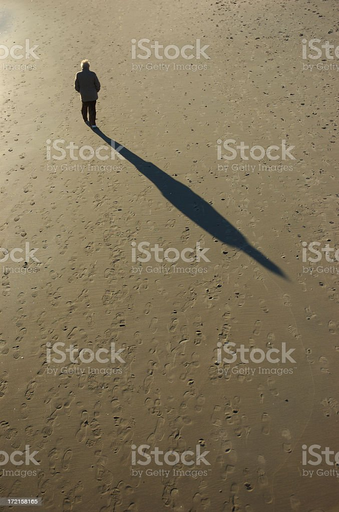 Senior Man Walking Casting Long Shadow on Beach stock photo