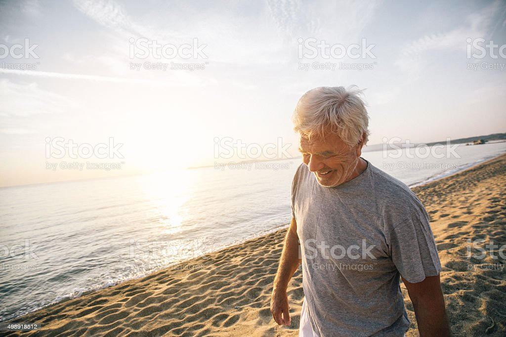 Senior man walking down the beach stock photo