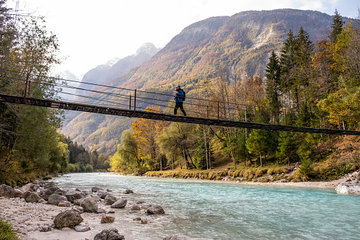 Senior Man walking on the Suspension bridge over Soča River in Julian Alps, Trenta, Bovec, Slovenia, Europe.