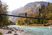 istock Senior Man walking on the Suspension bridge over the Soča River 1281492274