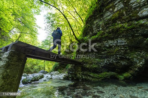 Adventurist exploring the paths of the Amazing Kozjak waterfall in Julian Alps canyon near Kobarid, Slovenia