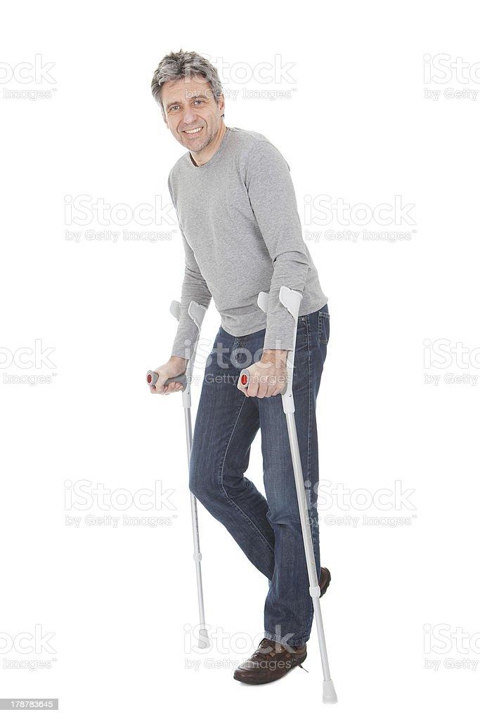 Senior man walking using crutches royalty-free stock photo