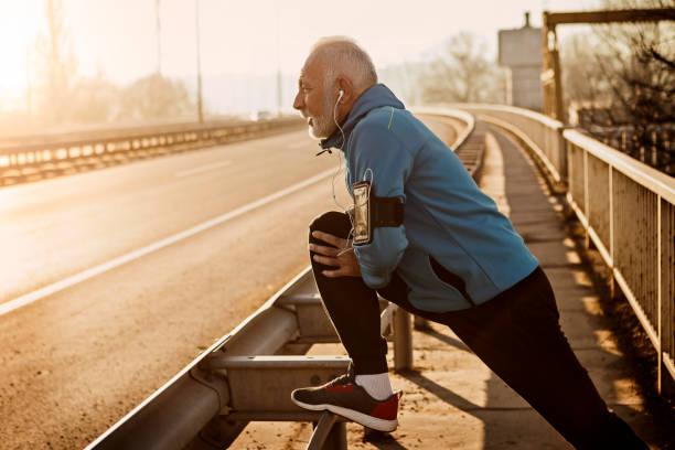 Senior woman Aufwärmen zum Joggen auf einer Stadtbrücke – Foto