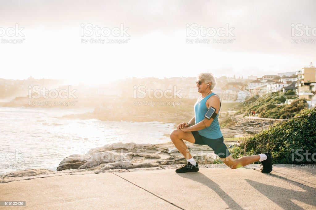 Senior man warms up for run stock photo