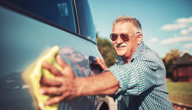 Senior man washing car stock photo