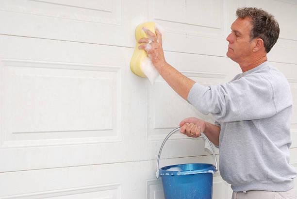 Senior man Washing the Garage Door. stock photo