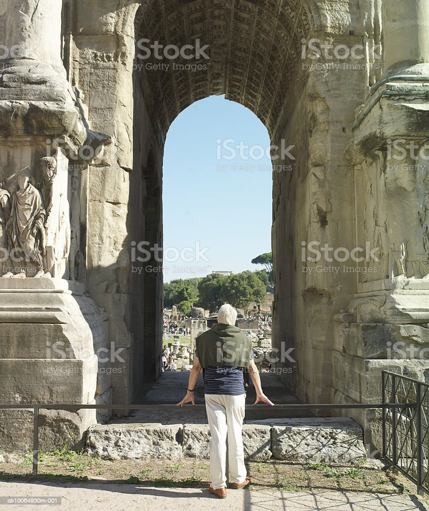 Senior man watching at ancient site, rear view foto de stock libre de derechos
