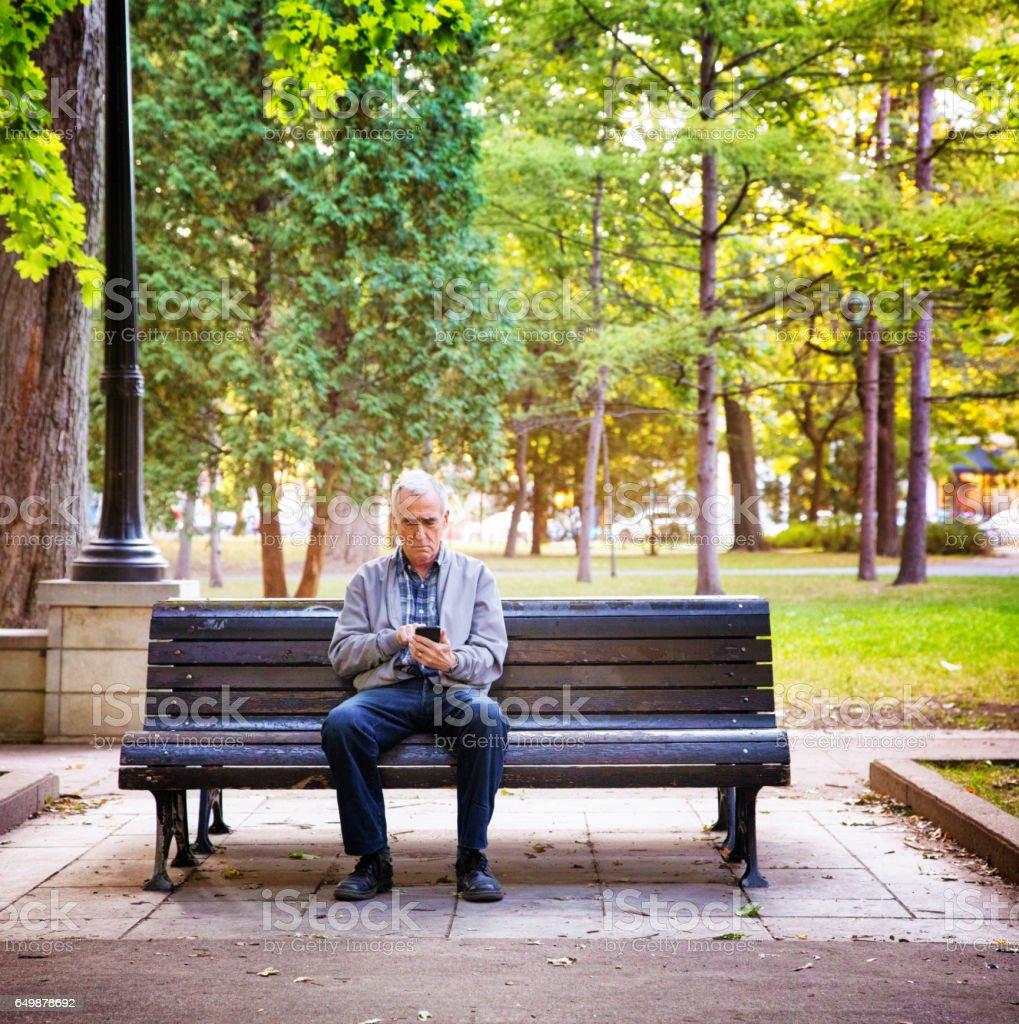 Senior homme regardant médias sur portable seul dans un parc public - Photo