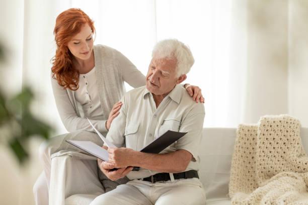 senior man kijken photobook tijdens bezoek van kleindochter thuis - senior fotoboek stockfoto's en -beelden
