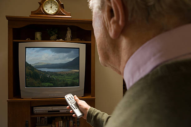 Senior man watching television Senior man watching television changing channels stock pictures, royalty-free photos & images