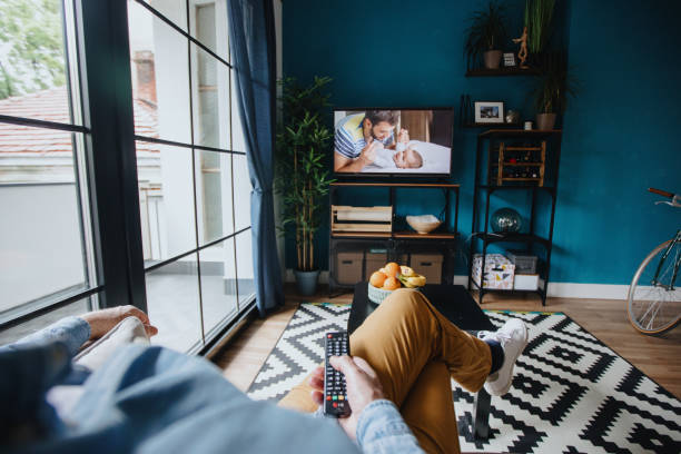 Senior man watching TV at home stock photo