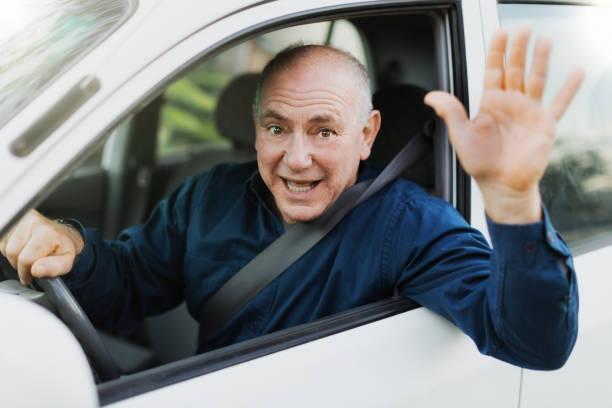 vagues d'homme senior pour saluer un ami comme il conduit sa voiture - homme faire coucou voiture photos et images de collection