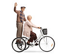 Senior man waving from a tricycle and senior woman riding isolated on white background