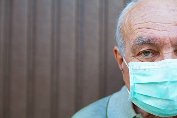 Senior man wearing a protective face mask stock photo