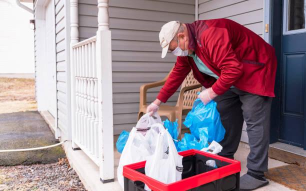 Senior Senior Senior trägt eine Schutzmaske und Handschuhe nimmt Lebensmittel aus den Mülltonnen links auf seiner Veranda in sein Haus während COVID-19 Pandemie Ausbruch. – Foto