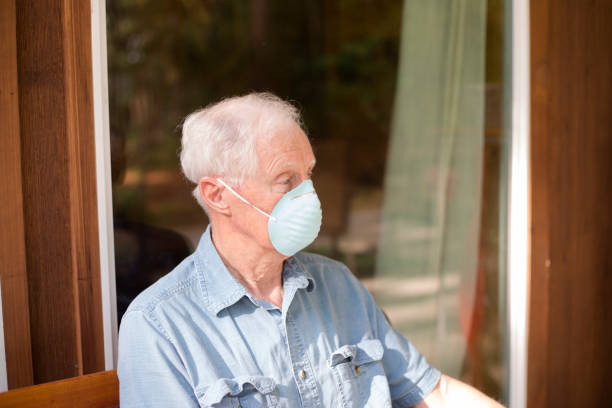 Senior man wearing COVID-19 mask.  He sits alone on bench outside. Lonely senior man sits outside on a bench.  He wears a COVID-19 face mask.  He is depressed. covid stock pictures, royalty-free photos & images
