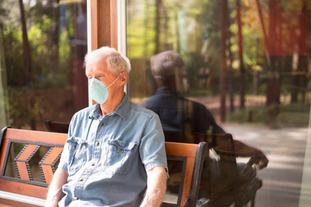 Senior man wearing COVID-19 mask.  He sits alone on bench outside. Lonely senior man sits outside on a bench.  He wears a COVID-19 face mask.  He is depressed. covid-19 stock pictures, royalty-free photos & images