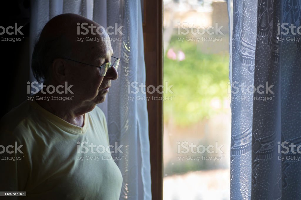 Man wearing yellow shirt and window with lace curtains