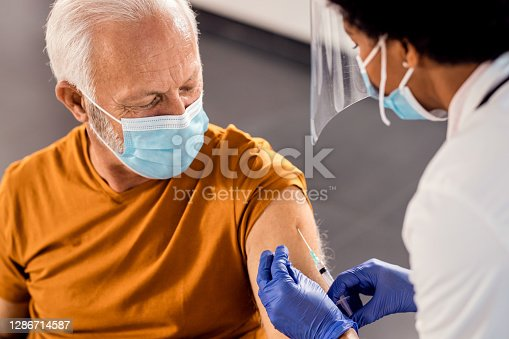 istock Senior man wearing face mask while receiving vaccine at medical clinic. 1286714587
