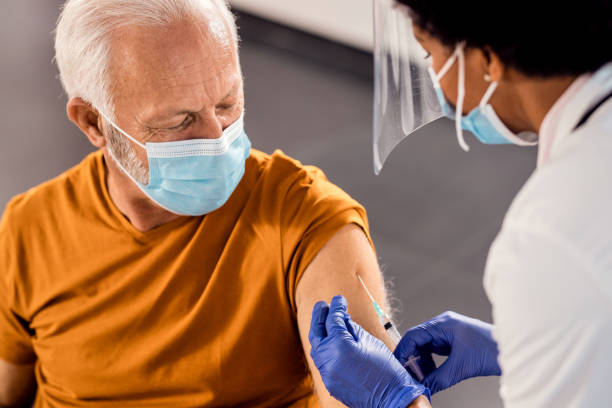 Senior man wearing face mask while receiving vaccine at medical clinic. Male senior patient getting vaccinated at medical clinic during coronavirus pandemic. covid vaccine stock pictures, royalty-free photos & images