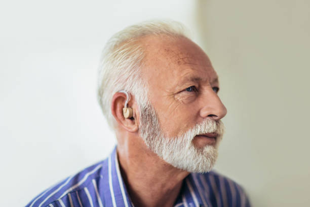 senior man wearing hearing aid - hearing loss stock pictures, royalty-free photos & images