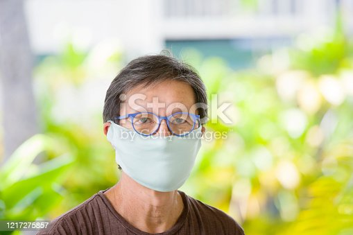 COVID-19, a senior adult man with a homemade face mask for Social Distancing. Outdoor portrait.