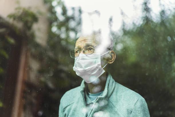 Senior man wearing mask looking through window stock photo
