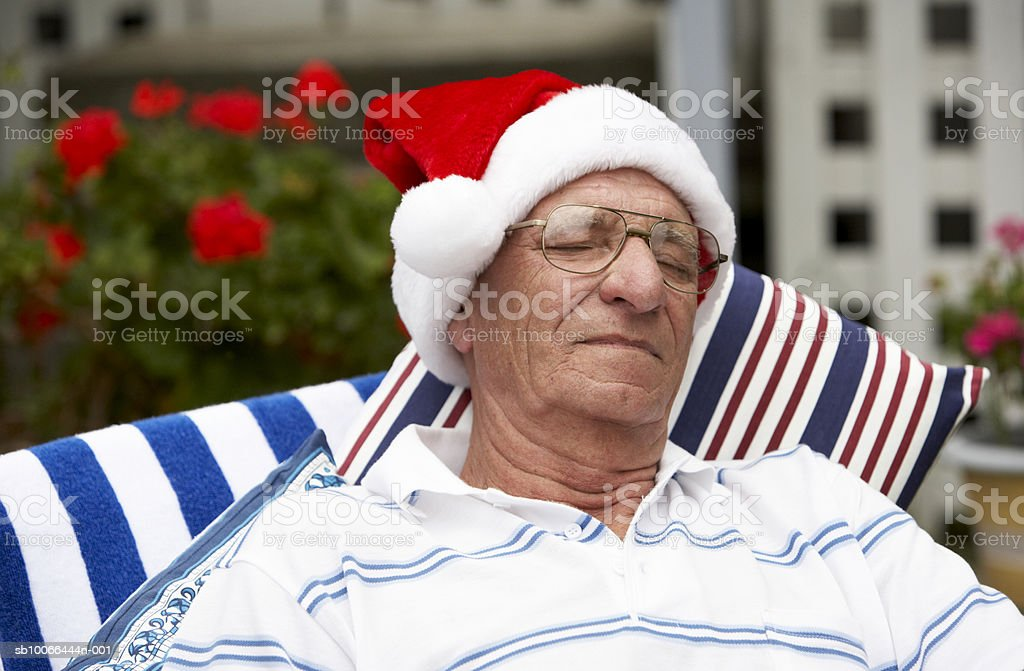 Senior man wearing Santa hat, sleeping outdoors royalty free stockfoto