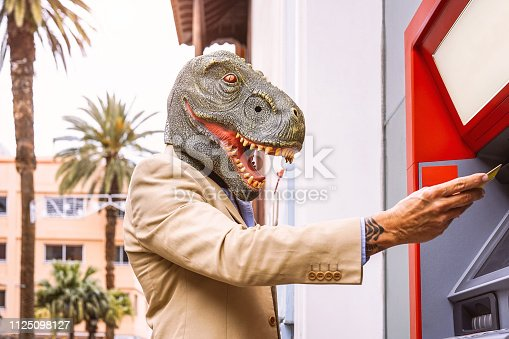 istock Senior man wearing t-rex dinosaur mask withdraw money from bank cash machine with debit card - Surreal image of half human and animal - Absurd and crazy concept of ATM advertise 1125098127
