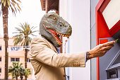 Senior man wearing t-rex dinosaur mask withdraw money from bank cash machine with debit card - Surreal image of half human and animal - Absurd and crazy concept of ATM advertise
