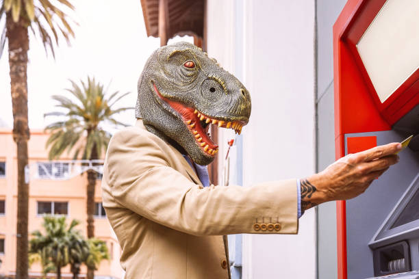 senior man wearing t-rex dinosaur mask withdraw money from bank cash machine with debit card - surreal image of half human and animal - absurd and crazy concept of atm advertise - банки и банкоматы стоковые фото и изображения