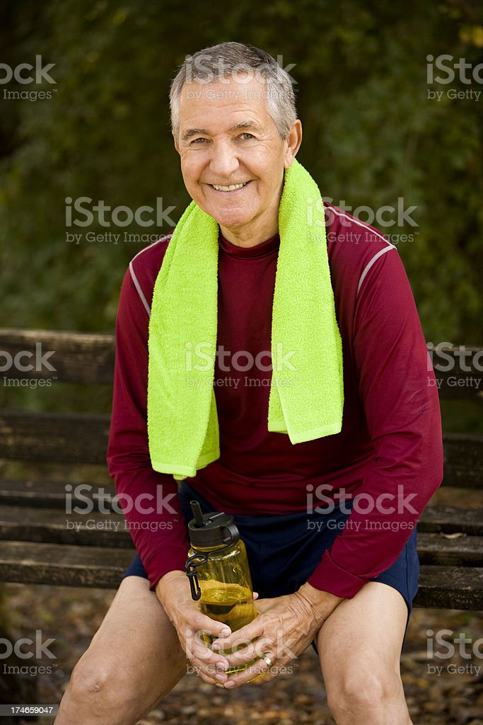Senior man wearing workout attire sitting on park bench royalty-free stock photo
