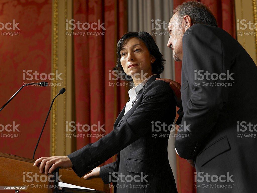 Alter Mann Flüstern für Politiker Frau stehend an Rednerpult – Foto