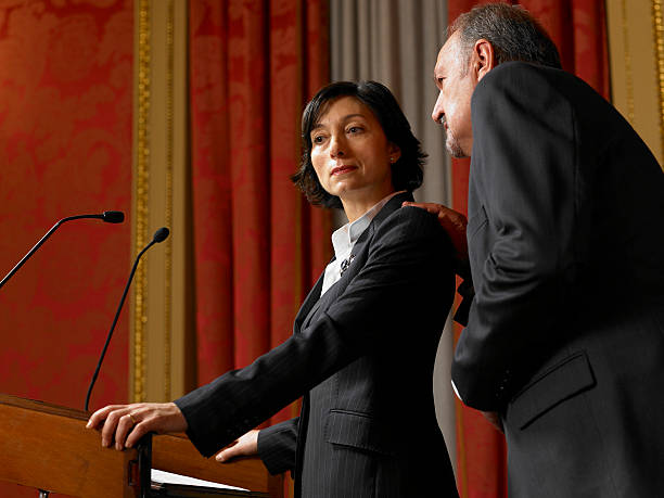 Senior man whispering to politician woman standing at lectern stock photo