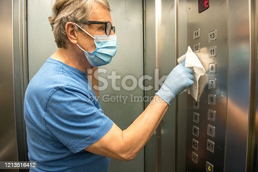 istock Senior Man Wiping Down the Inside of the Elevator for Covid-19, Europe 1213516412