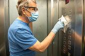 Senior man wiping down the elevator buttons, Slovenia, Europe. Nikon D850.