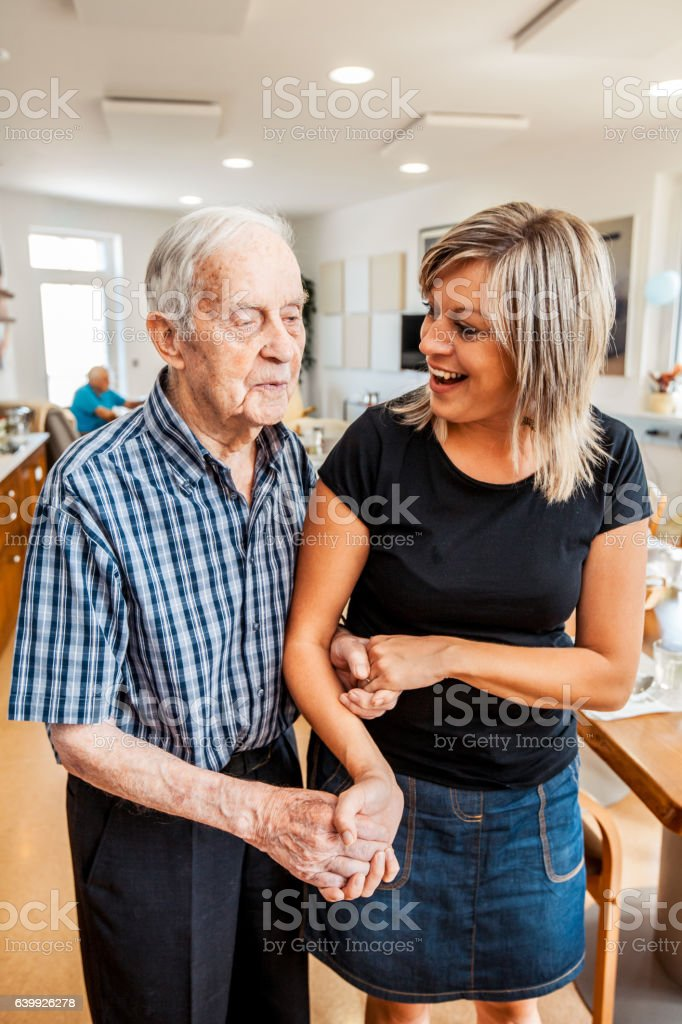 Senior Man with a Caregiver in an Elderly Daycare Center Lizenzfreies stock-foto
