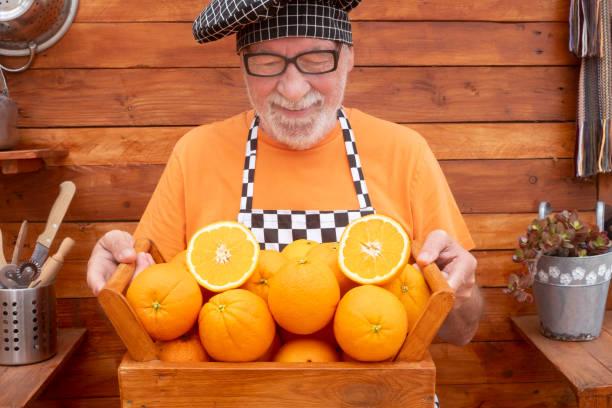 een hogere mens met een chef-kokglb houdt een mand hoogtepunt van sinaasappelen die aan vitaminen rijk zijn. een gezonde levensstijl - oldman chef's cap hat stockfoto's en -beelden