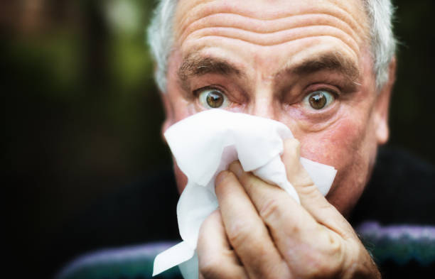 Senior man with a cold blows his nose on a tissue, wide-eyed Man blowing his nose outdoors. respiratory disease stock pictures, royalty-free photos & images