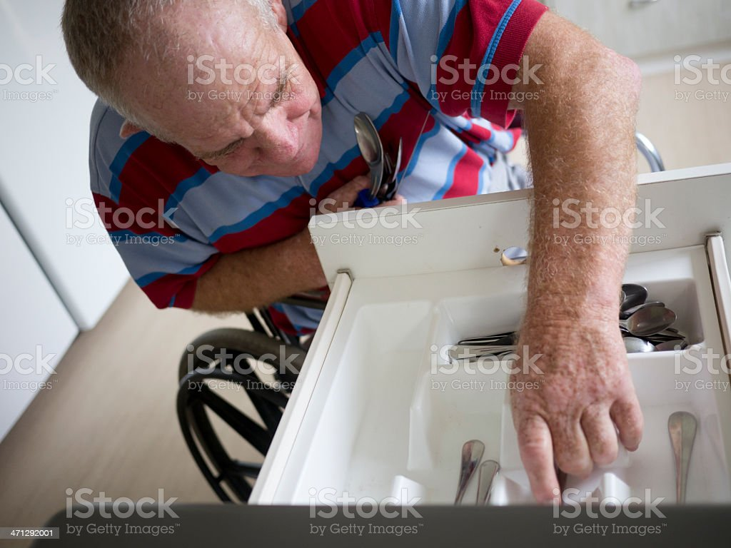 Senior man with a disability at cutlery drawer stock photo