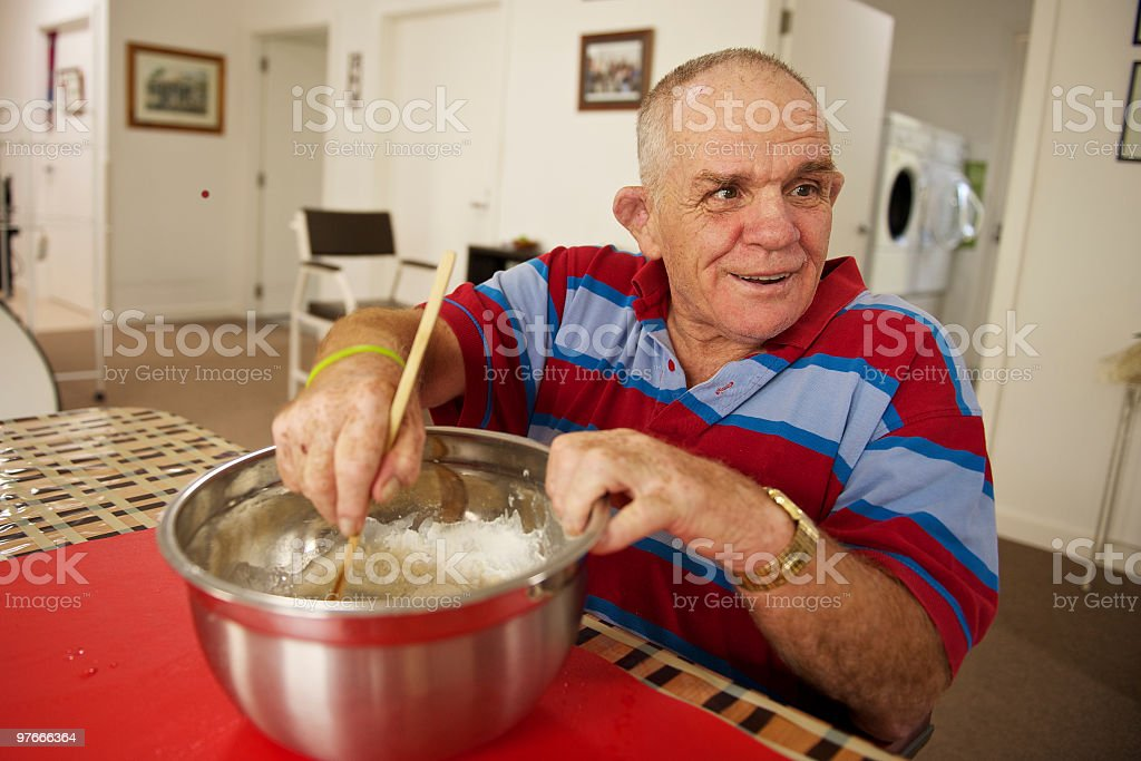 Senior man with a disability at home mixing flour. stock photo