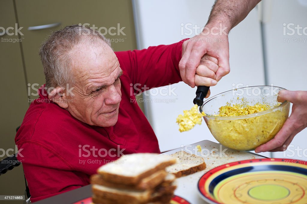 Senior Man with a Disability being helped in kitchen stock photo