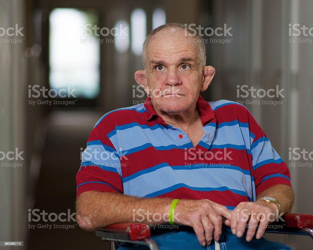 Uomo anziano con una disabilità suo ingresso nel corridoio. foto stock royalty-free