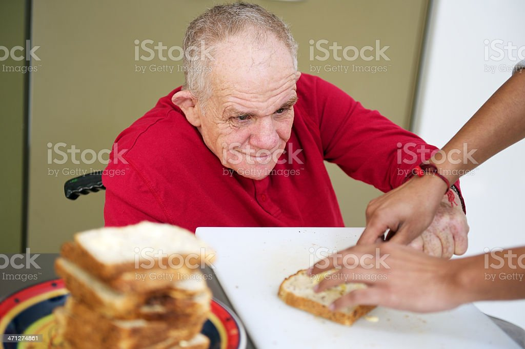Senior Man with a disability making sandwiches stock photo