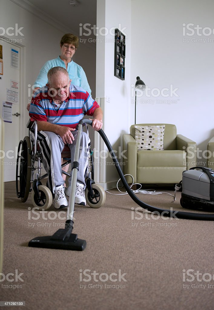 Senior man with a disability vacuuming floor stock photo